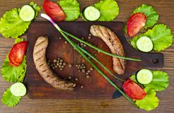 Bavarian sausages on a cutting board with vegetables royalty free stock image
