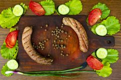 Bavarian sausages on a cutting board with vegetables royalty free stock photography