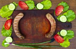 Bavarian sausages on a cutting board with vegetables royalty free stock photos