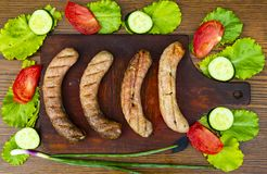 Bavarian sausages on a cutting board with vegetables. Cucumber, tomato, green salad. View from above. Place for text stock images
