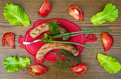 Bavarian sausages on a cutting board with vegetables. Cucumber, tomato, green salad. View from above. Place for text royalty free stock images