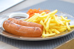 Bavarian sausages grilled with fries, carrots in Korean and sauce. On a large plate Royalty Free Stock Photos