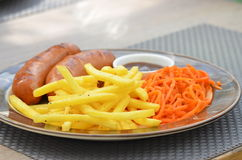 Bavarian sausages grilled with fries, carrots in Korean and sauce. On a large plate Stock Photos