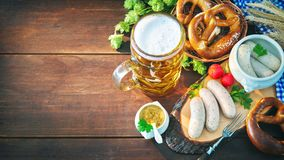 Bavarian sausages with pretzels, sweet mustard and beer mug on r Royalty Free Stock Photos