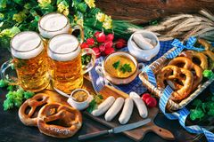 Bavarian sausages with pretzels, sweet mustard and beer mugs on Royalty Free Stock Images