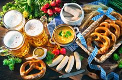 Bavarian sausages with pretzels, sweet mustard and beer mugs on Stock Image