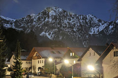 Bavarian village night scene. Picturesque Bavarian village illuminated at night in front of snow capped mountains, Germany Royalty Free Stock Photography