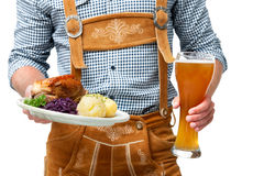 Bavarian waiter. Food and drinks are served by waiter wearing traditional Bavarian leather trousers Stock Photo