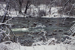 Bavarian winter landscape, green running waters framed by white Stock Photo