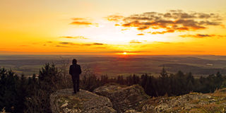Bavarian Winter Sunset. Young man with a wistful gaze into the distance on a warm and dark winter sunset in Bavaria, Germany Stock Image