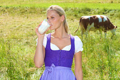 Bavarian Woman. Beautiful young bavarian woman standing outside and drinking milk stock photography