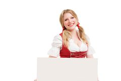 Bavarian woman in dirndl, holding blank signboard. Royalty Free Stock Photo