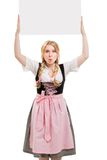 Bavarian woman in dirndl, holding blank signboard. Royalty Free Stock Photography