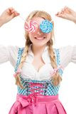 Bavarian woman in dirndl, holding lollipop. Royalty Free Stock Images