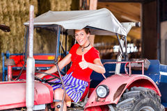 Bavarian woman with dress driving tractor Royalty Free Stock Images