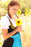 Bavarian Woman holding Sunflower. Portrait of beautiful bavarian woman holding a sunflower with a background of sunflowers Royalty Free Stock Photography