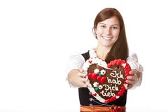 Bavarian woman in love holds Oktoberfest heart. Royalty Free Stock Images