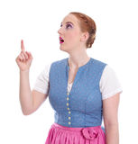 Bavarian woman pointing up in dirndl - isolated on white Stock Images