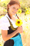 Bavarian Woman with Sunflower. Portrait of beautiful bavarian woman holding a sunflower with a background of sunflowers Royalty Free Stock Photo