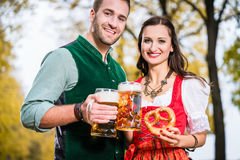 Bavarians in Tracht with Beer and Pretzel in autumn Stock Image