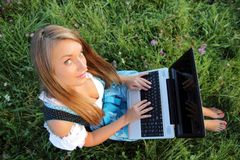 Bavarina Woman in Meadow with Laptop from above Royalty Free Stock Image