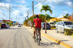 BAVARO, REPÚBLICA DOMINICANA - 09 01 2015: Montar a caballo indefinido del hombre en la bicicleta a lo largo del camino de ciudad foto de archivo