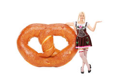 Bawarska dziewczyna opiera na ogromnym preclu zdjęcie stock