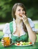 Bawarska kobieta w dirndl łasowaniu przy piwo ogródem Fotografia Royalty Free