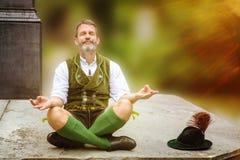 Bawarski mężczyzna obsiadanie na ściennym i medytować obrazy royalty free