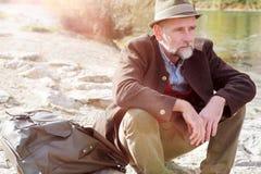 Bawarski mężczyzna w jego 50s obsiadaniu rzeką obraz royalty free