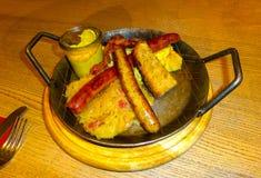 Bawarskie kiełbasy piec na grillu na drewnianej round desce z musztardą, czerwonym pieprzem i ziele na drewnianym nieociosanym tl zdjęcie royalty free