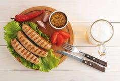 Bawarskie kiełbasy piec na grillu na drewnianym round piwie i desce zdjęcie stock