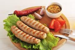 Bawarskie kiełbasy piec na grillu na drewnianej round desce Zdjęcie Stock