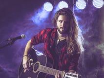 Bawić się gitarę akustyczną na scenie zdjęcie royalty free