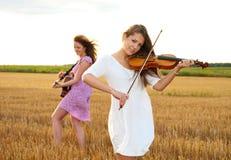 Bawić się gitarę dwa młodej kobiety Zdjęcia Royalty Free