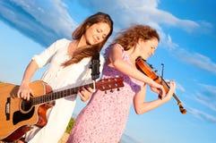 Bawić się gitarę dwa młodej kobiety Fotografia Stock