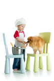 Bawić się grę Dzieciak chłopiec bawić się szefa kuchni z zwierzęciem domowym Dziecko weared kucharz karm pies Fotografia Stock