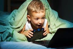 Bawić się gra wideo chuje w łóżku zdjęcie stock