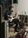 Bawić się jego gitarę elektryczną w studio nagrań zdjęcie stock