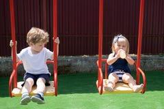 Bawić się jest zabawą Mały brat i siostra cieszymy się bawić się wpólnie Mali dzieci z blondynem na huśtawce Dziewczyna i chłopie obraz stock
