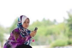 bawić się kobiety jej telefon komórkowy Zdjęcia Stock