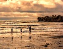 Bawić się na plaży pod zima zmierzchem Zdjęcie Stock