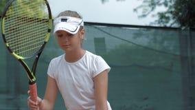 Bawi się aktywność i przygotowywa dla gry, Śliczni nastoletni dziewczyna gracza w tenisa uderzenia balowi na ziemi na sądzie zdjęcie wideo