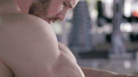 Bawi się aktywność, mięśniowy bodybuilder mężczyzna robi władz ćwiczeniom na mięśniach ręki na symulancie podczas siły zbiory