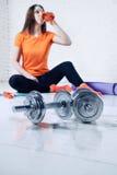 Bawi się dysponowanej kobiety pozuje i pije wodę w gym z wyposażenia, dumbbell i szkolenia ochraniaczem, Zdjęcie Royalty Free