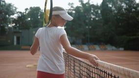 Bawi się hobby, fachowy nastoletni dziewczyna gracz w tenisa z kantem dotyka tenis sieć i chodzi wzdłuż sądu póżniej zbiory