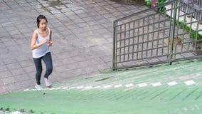 Bawi się kobiety używa telefonu komórkowego bieg w miasto miastowym budynku Zdjęcia Stock