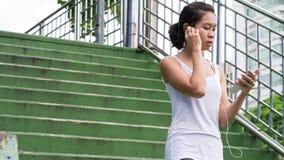 Bawi się kobiety używa telefonu komórkowego bieg w miasto miastowym budynku Zdjęcia Royalty Free