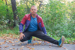 Bawi się mężczyzna rozciąganie przy parkową jesienią, robi ćwiczeniom Sprawności fizycznych pojęcia Obrazy Stock