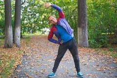 Bawi się mężczyzna rozciąganie przy parkową jesienią, robi ćwiczeniom Sprawności fizycznych pojęcia Fotografia Royalty Free
